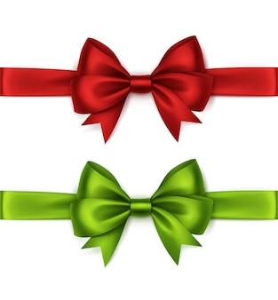 Набор блестящих красных светло-зеленых атласных бантов и лент, вид сверху крупным планом, изолированные на белом фоне