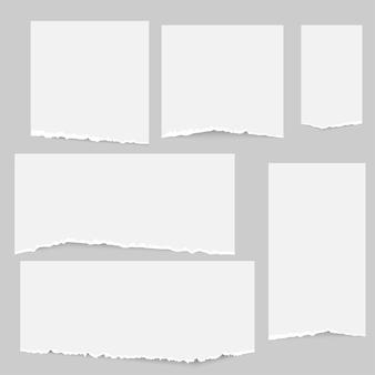 Набор полосок рваной бумаги для заметок, застрявших на сером