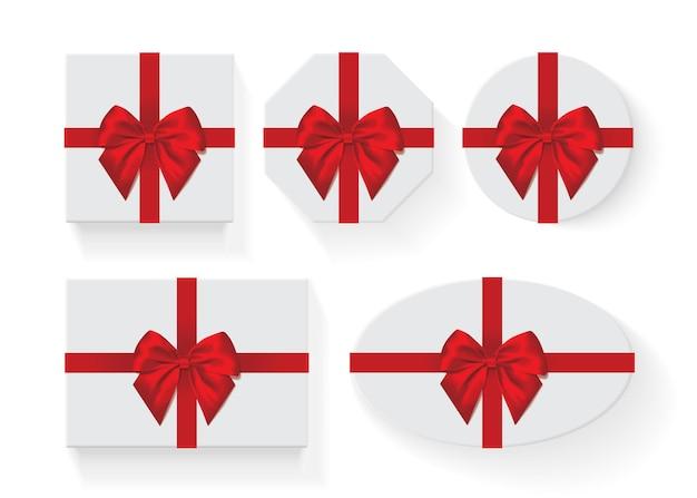 Набор белых коробок с красным большим подарочным бантом, изолированным на белом
