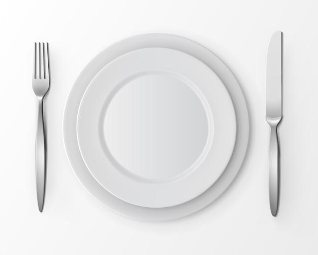 Набор белых пустых плоских круглых пластин с вилкой и ножом