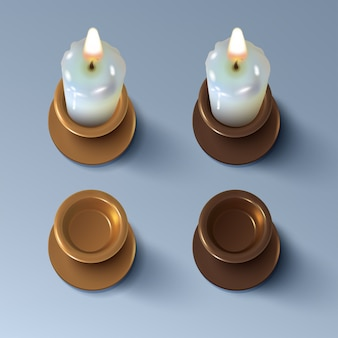 Set of realistic burning candles and vintage brass or copper candlesticks
