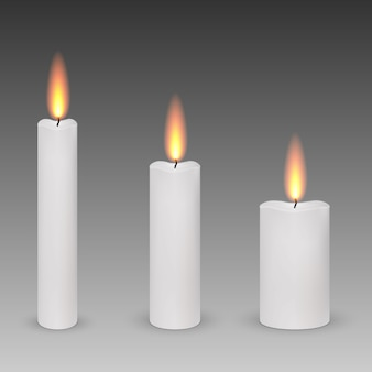 Set of realistic paraffin burning candles isolated