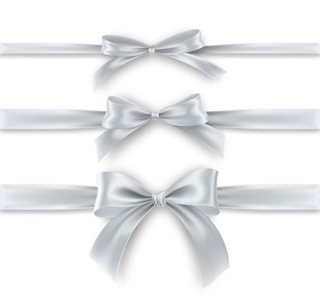 白い背景の上の銀の弓とリボンを設定します。リアルなシルバーのリボン。