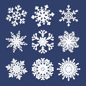 Set of  white paper snowflakes isolated on blue background.