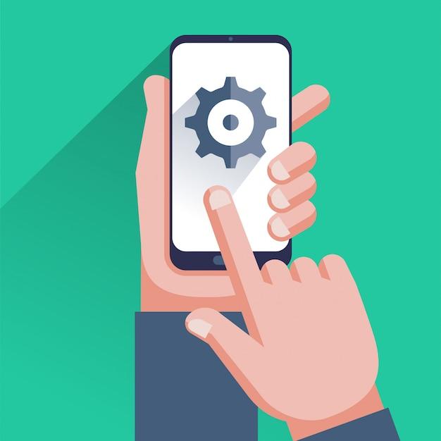 Настройки на экране смартфона. рука держит мобильный телефон, пользователь касаясь значок шестеренки