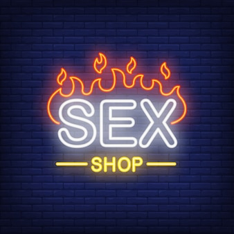 Sex shop lettering on fire. Neon sign on brick background.