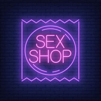 Sex shop neon sign. condom package on brick wall.