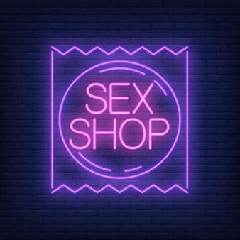 Секс-магазин неоновый знак. пакет презервативов на кирпичной стене.