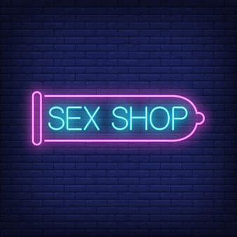 Sex shop neon sign. pink condom on brick wall. night bright advertisement.