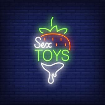 Клубника с надписью sex toys. неоновый знак на фоне кирпича.