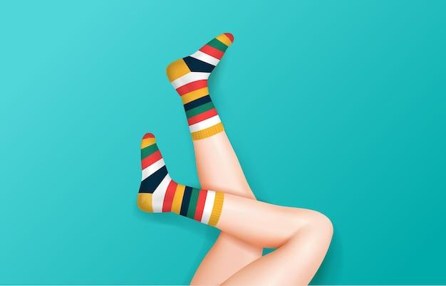Sexy female legs in stripe socks raised up wearing on blue