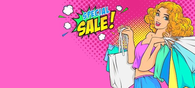 Сексуальная удивленная молодая женщина, держащая хозяйственные сумки и речевой пузырь специальной распродажи