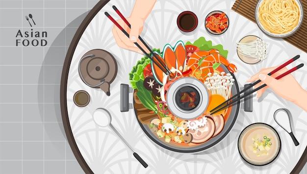 Сабу-сябу и сукияки в горячем горшке в ресторане, рука, держащая палочки для еды, ест сябу-сябу