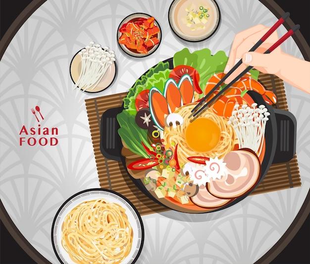 Сабу-шабу и сукияки в горячем горшке в ресторане, рука, держащая палочки для еды, ест шабу