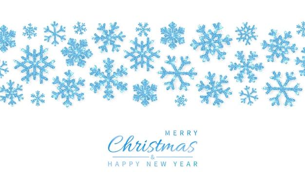 白い背景に輝くキラキラ輝く青い雪片。クリスマスと新年の背景。