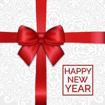 Смычок атласной ленты сияющего нового года праздника красный на белой кружевной орнаментальной предпосылке.