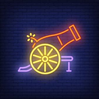 Shooting cannon neon icon. Bright circus gun on dark brick wall background