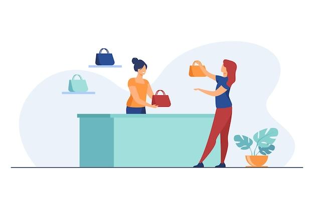 Assistente di negozio che aiuta il cliente femminile a scegliere la borsa