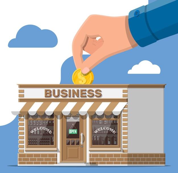 Здание магазина или коммерческая недвижимость, рука с монетой. продвижение бизнеса в сфере недвижимости, краудфандинг стартапов. продажа, покупка нового бизнеса. небольшой экстерьер магазина в европейском стиле. плоские векторные иллюстрации