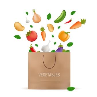 Бумажный пакет для покупок, в который падают свежие овощи - картофель, морковь, огурец, лук, перец, помидор, баклажан, баклажан, чеснок. вегетарианские или веганские органические продукты. на белом
