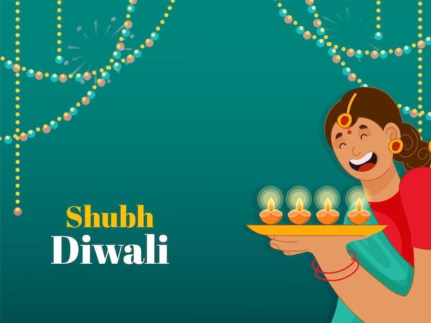 緑の背景に点灯している石油ランプ(diya)のプレートを保持しているインドの若い女性とshubh(幸せ)ディワリの概念。