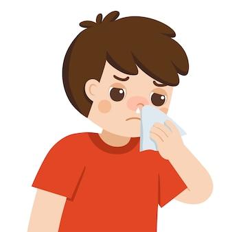 Больной милый мальчик с холодным и насморком чихает бумажной салфеткой. симптомы гриппа.