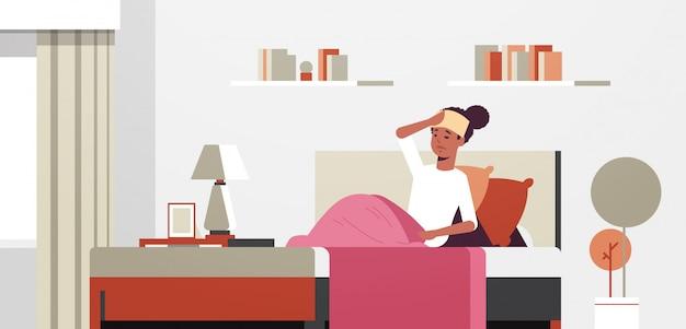 Больной женщина с влажным полотенцем на лбу нездоровая афроамериканец девушка снижение лихорадка страдает от вируса гриппа простуды концепция современная горизонтальный гостиная полная длина