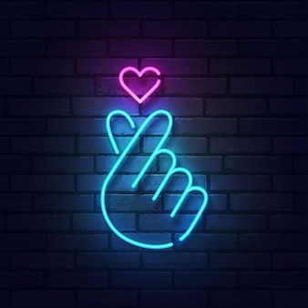 Sign of finger heart with colorful neon lights isolated on brick wall.