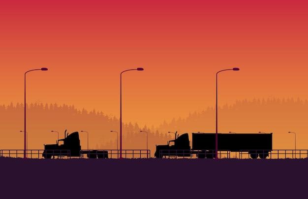 オレンジ色のグラデーションで森の山の風景とトレーラーコンテナとシルエットアメリカントラック