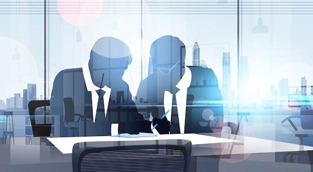 Силуэт бизнес-мужчина сидит за столом
