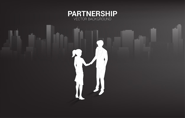 Silhouette of businessman and businesswoman handshake with city background. concept of team work partnership and cooperation.