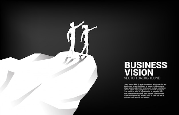 Silhouette of businessman and businesswoman point forward from mountain cliff. concept of business market vision mission start up