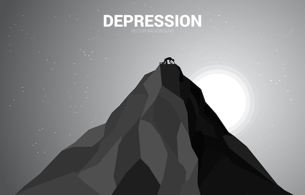 Silhouette of businessman crawling on top of mountain. concept for depression of success business.