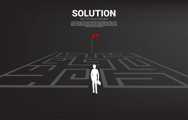 Silhouette of businessman enter to maze to red flag. business concept for finding solution and reach goal