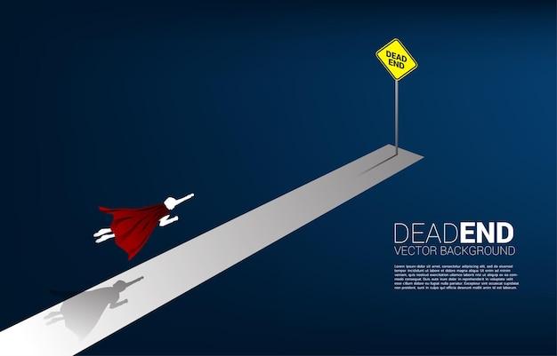 실루엣 사업가는 막다른 표지판을 가로질러 날아갑니다. 비즈니스의 장애물과 도전에 대한 배경 개념