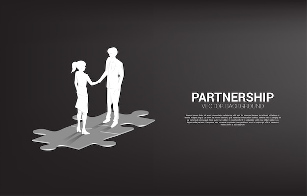 Silhouette of businessman handshake on jigsaw. concept of team work partnership and cooperation.