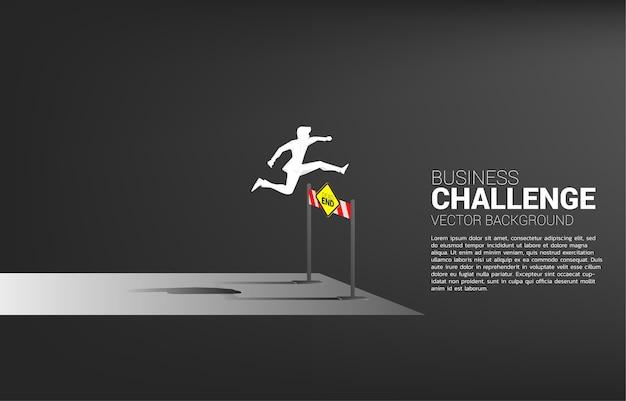 行き止まりを飛び越えるシルエットのビジネスマンは障害物をハードルします。ビジネスにおける障害と挑戦の背景概念