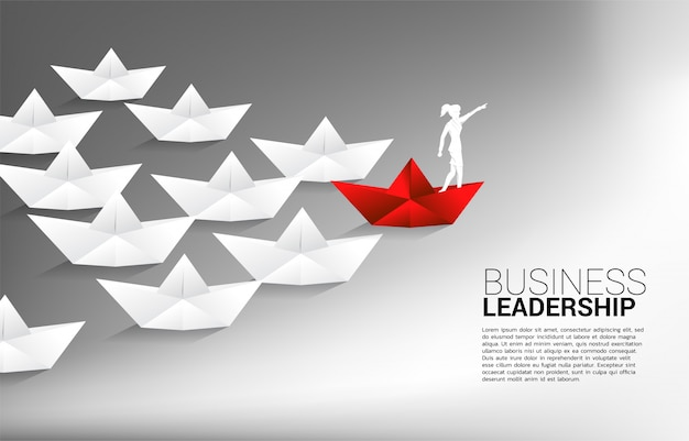 Silhouette of businessman point forward on red origami paper ship leading group of ship. business concept of leadership and vision mission.