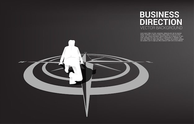 Silhouette of businessman ready to run from center of compass on floor.