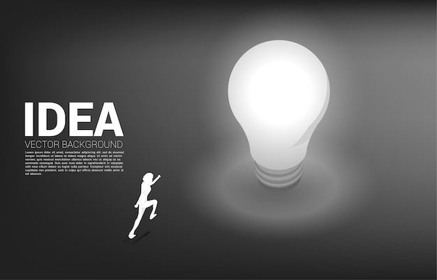 Silhouette of businessman running to light bulb