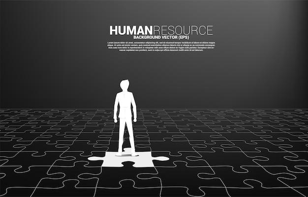 Silhouette of businessman stand on match jigsaw piece