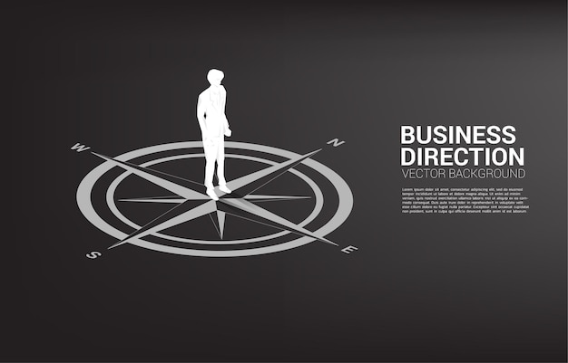 Silhouette of businessman standing at center of compass on floor.