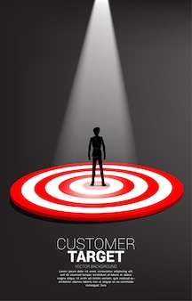 Silhouette of businessman standing on center of dartboard with spot light .