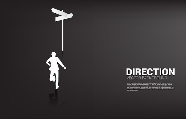 Silhouette of businessman standing at direction signage. concept of time to make decision in business direction