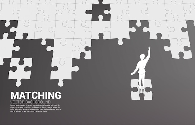 Silhouette of businessman standing on final jigsaw piece.