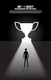 출구 문 모양 트로피에서 빛에 서 있는 실루엣 사업가. 승자와 챔피언에 대한 경로의 비즈니스 개념