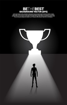 Silhouette businessman standing in light from exit door shape trophy. business concept of route to winner and champion
