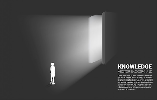 Silhouette of businessman standing in light from open book.