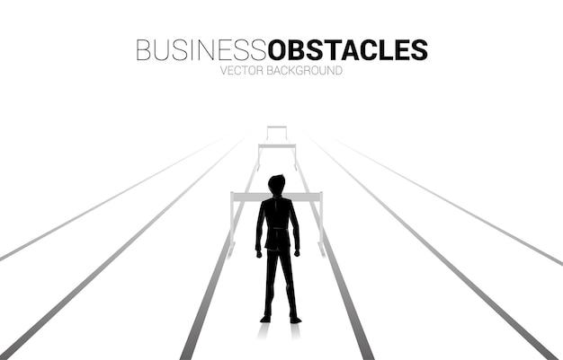 장애물 장애물과 함께 서 있는 실루엣 사업가. 비즈니스의 장애물과 도전에 대한 배경 개념