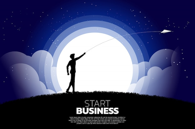 Silhouette of businessman throw out origami paper airplane at night. business concept of start business and entrepreneur